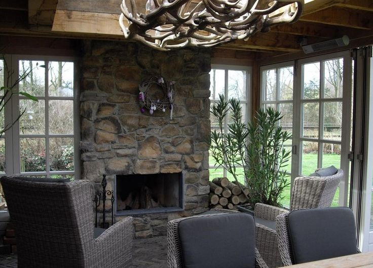 caminetti-in-pietra-lampadario-design-poltrone-vimini-pianta-sempreverde-finestre