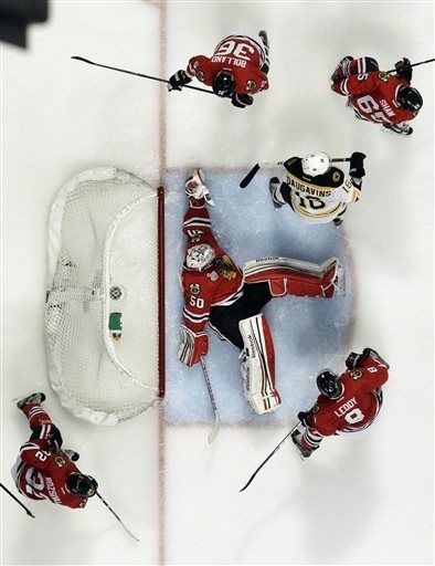Chicago Blackhawks goalie Corey Crawford (50) makes a save during the first overtime period of Game 1 in their NHL Stanley Cup Final hockey series against the Boston Bruins, Thursday, June 13, 2013, in Chicago. (AP Photo/Nam Y. Huh)