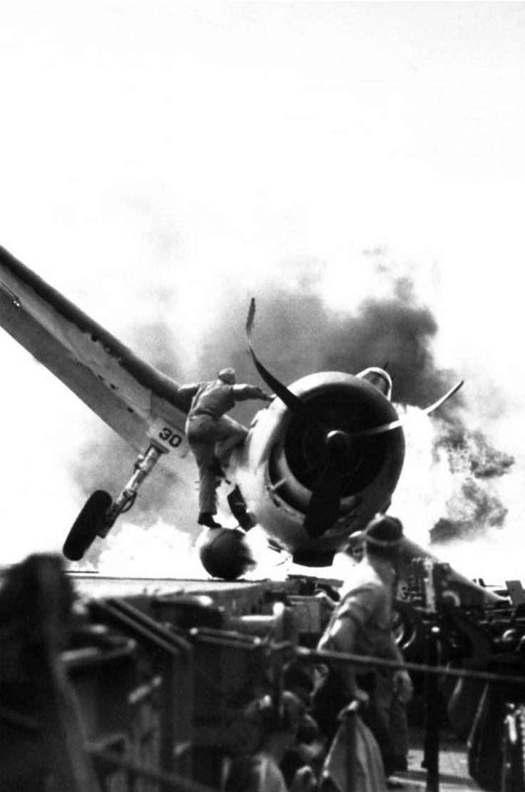 The cash landing of a F6F Grumman Hellcat on the deck of the USS Enterprise while en route to attack Makin Island. Lietenant Walter Chewning the catapult officer is climbing up to assist pilot Ensign Byron Johnson in escaping. November 1943