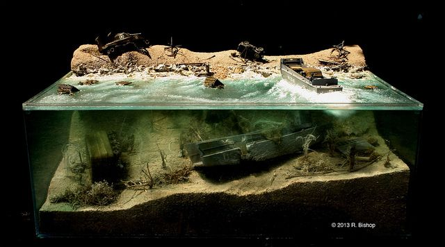 """Ramesh Bishop ModelCrafters was commissioned to create a WWII D-Day diorama depicting invasion damage on Normandy Beach both on the beachhead and below the water. Plexi Diorama shot outside against a dark background Model Number/Name: Plexi WWII D-Day Diorama, June 6, 1944 • Destruction above and below water Photo Credit: © 2013 R. Bishop Scale: 1/48 scale, Plexi model overall dimensions: 20"""" deep x 29"""" wide x 10"""" high Mixed Media Photo No. 9908 www.modelcrafters.com"""