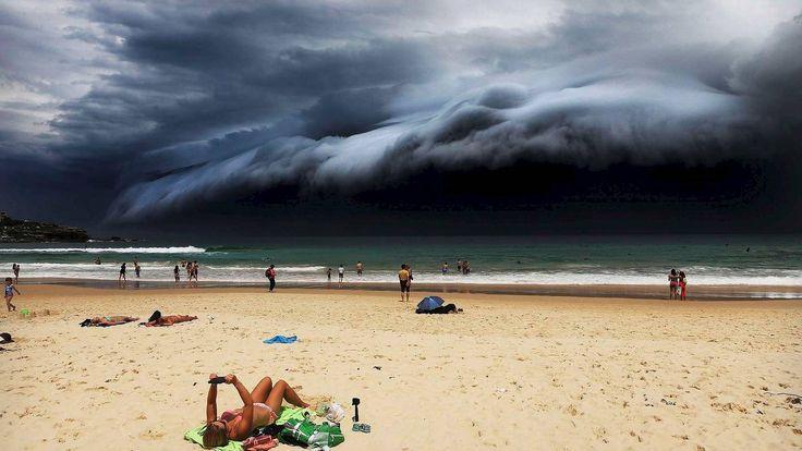 En solbader på Bondi Beach er uvitende om om de illevarslende skyene som nærmer seg. Det spektakulære været, som ruller inn fra havet, farger himmelen svart og medfører et voldsomt tordenvær. Dette skjer bare et par ganger i året.