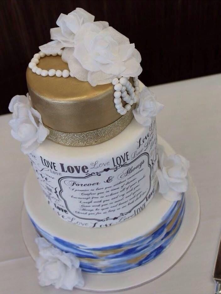 A stunning wedding cake with blue and gold water colour and scripted wedding vowels give a personal touch. Delicate wafer paper flowers complete this design. Made by Michelle-Marie's Kitchen