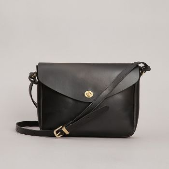 Black Frank Leather Shoulder Bag: Medium shoulder bag made from the finest vegetable tanned leather.  Lined in beige cotton drill, with one interior zip pocket and and two patch pockets.  Exterior pocket on the back.  Brass turnlock fastening.  Long buckled strap 123cm.  Made in England.