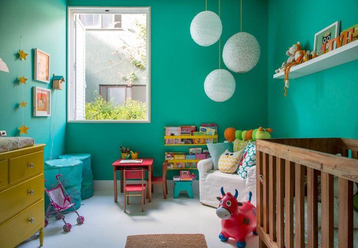 Immagine stanzetta neonato con le pareti verde turchese con vari decorazioni ludiche e colorate per sedurre il bambino - stile moderno