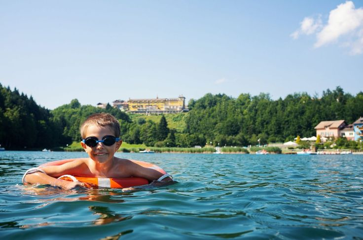 Young kid swimming in Lavarone lake with life buoy. Trentino Alto Adige region, Italy.