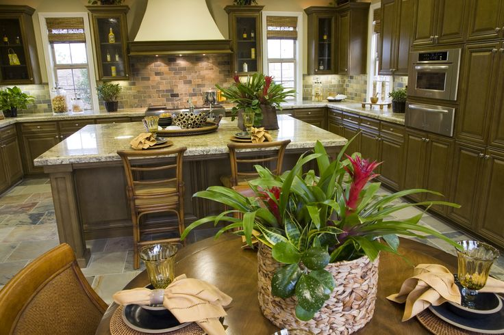 This spacious U-shaped kitchen has high-end appliances and fixtures. Tropical houseplants and display jars accessorize the countertops.