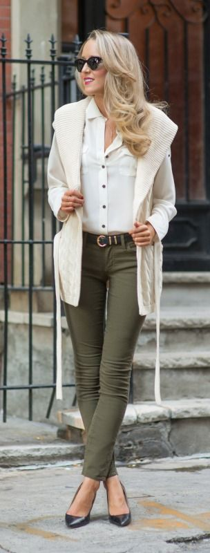olive green skinny jeans, ivory silk blouse, ivory cable knit sleeveless cardigan + classic black pumps