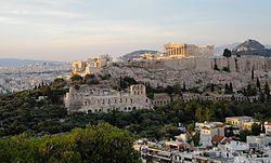 "The Acropolis of Athens (Greek: Ακρόπολη Αθηνών) is an ancient citadel located on a high rocky outcrop above the city of Athens and containing the remains of several ancient buildings of great architectural and historic significance, the most famous being the Parthenon. The word acropolis comes from the Greek words ἄκρον (akron, ""edge, extremity"") and πόλις (polis, ""city"")."