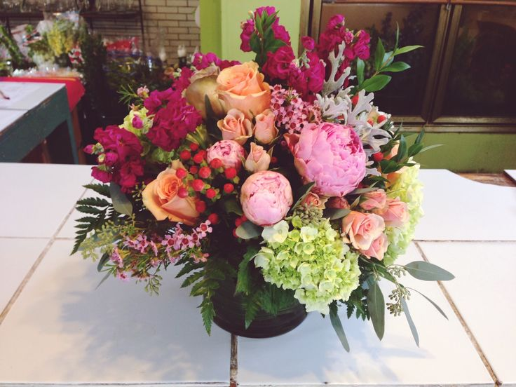 A spectacular arrangement with green hydrangeas, peach roses, peonies, maroon stock and much more!