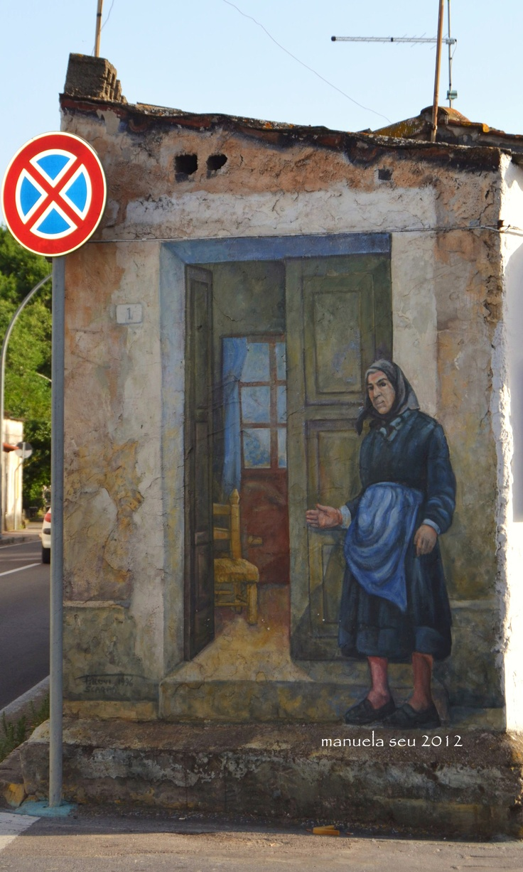 """#Sardegna #Sardinia     """"Zia Benvenuta"""" di Angelo Pilloni '96 - Murales rivolto al visitatore che arriva a San Sperate, raffigura una donna anziana del paese, che aprendo la porta della sua casa, rivolge un saluto di benvenuto in segno di ospitalità."""
