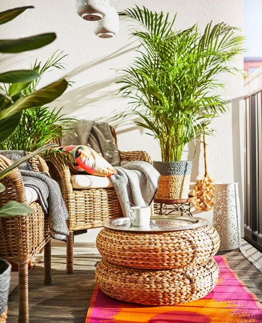 Two wicker armchairs, two stools stacked to make a table, plants and bright rugs sit on a balcony.
