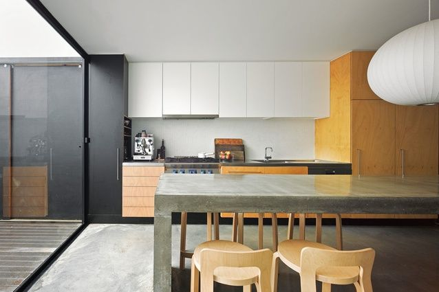 A long polished concrete bench dominates the kitchen.   Surry Hills House, Sydney, Australia, Anthony Gill Architects