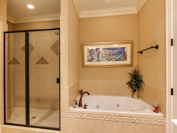 Side by side tub and shower with wall between them