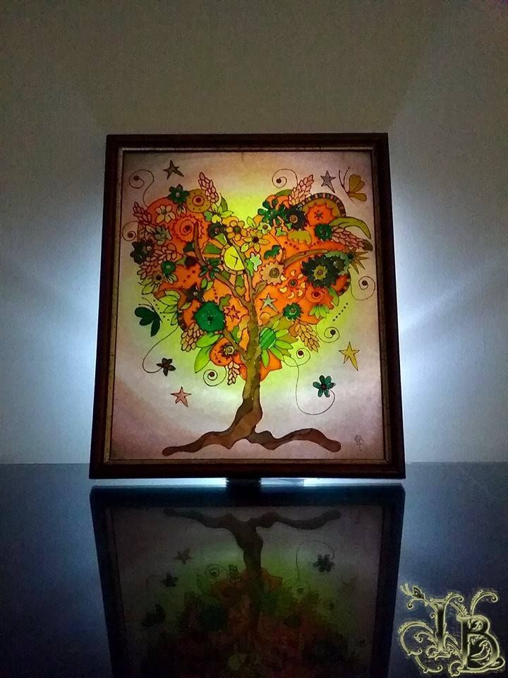 """Glass painting looks most beautiful in the evening when illuminated by light. Mixed Media Glass Painting in wooden frame called """"Tree Of Life"""". Size 30x25.  Using special transparent, opaque and pearl colors to make light effects.  Applying permanent waterproof paint. Finished with crystal resin made to perfection."""