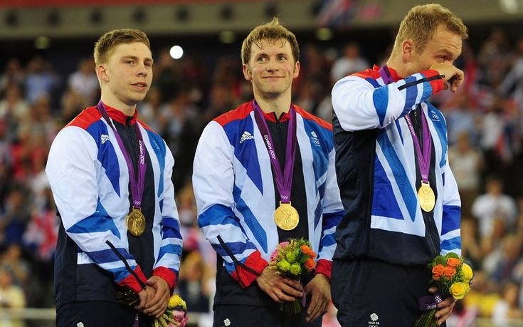 Philip Hindes, Jason Kenny and Sir Chris Hoy of Great Britain receive their gold medals after setting a new world record in the Men's Team Sprint Track Cycling final in the Velodrome