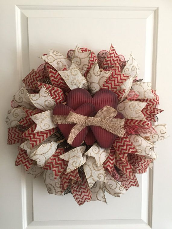 This beautiful heart wreath is done with red and black burlap mesh. Decorated with a red zigzag print burlap ribbon and a cream with gold glitter swirl print ribbon. Centered with triple hearts made out of wood with a burlap bow in the middle. Approx. 20 inches