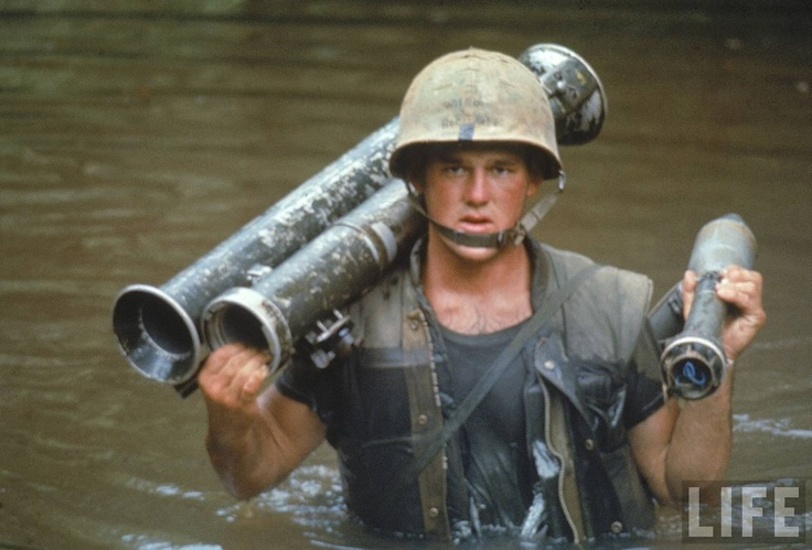 US Marine Phillip Wilson carrying rocket launcher across stream during fighting near the DMZ during the Vietnam War.