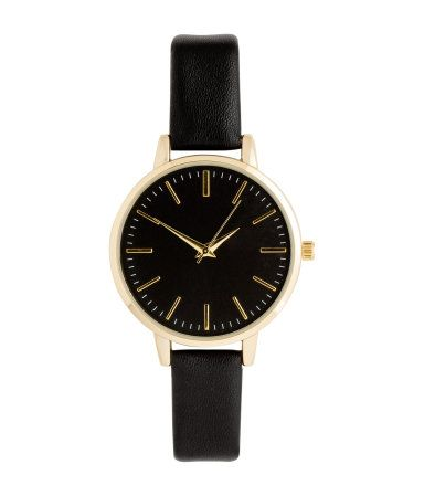 Black. Metal watch with a narrow, adjustable strap in imitation leather with a metal buckle. Width of strap 1/2 in., overall length 8 1/2 in. Diameter of