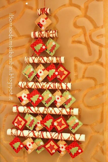 Calendario dell'avvento - advent calendar  Materiali semplici e di riciclo quest'anno per il calendario dell'Avvento.  - tubi di cartone  - acrilico panna  - nastro  - carta da regalo  Ho ricavato i pacchettini cucendo dei quadrati di carta regalo.