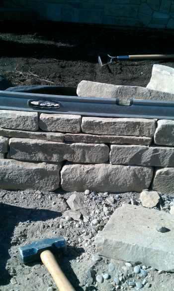 How to build a dry stack stone wall. Step-by-step detailed but not tedious instructions with pictures and a video.
