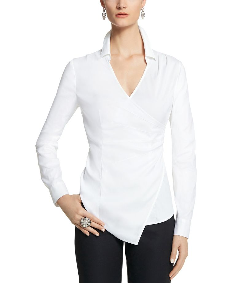 Essential white shirt reimagined with a graceful wrap front and starburst darts at the waist. Stretch fit. Pull on over head. Point collar. Pleats at shoulders. Long sleeves with two-button cuffs. Hidden side zip opens from the bottom. 78% cotton, 19% nylon, 3% spandex. Machine wash. Imported. Hits at lower hip (28.5