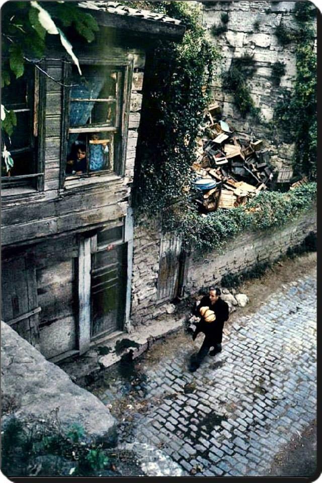 Camda bekleyen bir çocuk,evine ekmek götüren bir baba..1970'ler Fotoğraf : Ara Güler