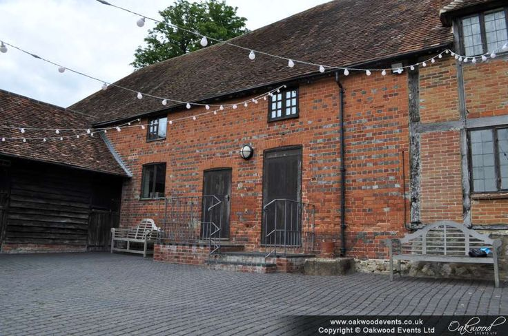 Festoon lights over the courtyard at Nether Winchenden Carriage Barn for a summer wedding