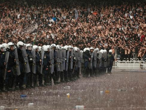 Athens, Greece - Policemen stand guard under heavy rain in front of PAOK Salonika fans before their Greek Cup soccer final against Panathinaikos at Athens' Olympic Stadium on April 26, 2014.