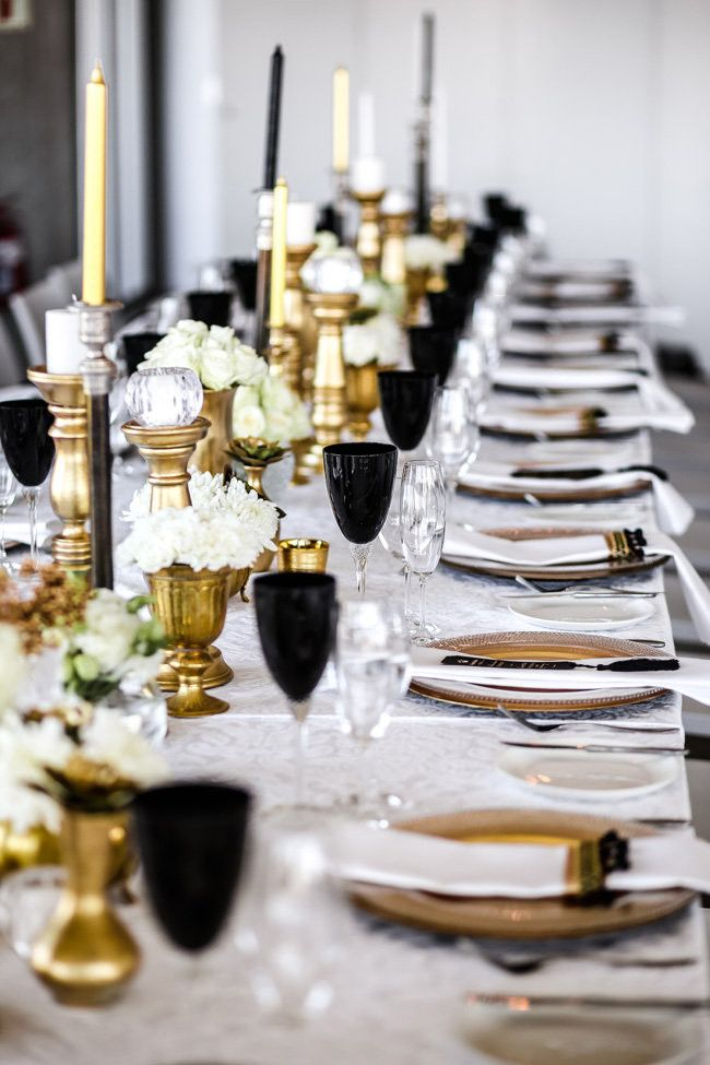Classic Elegant Gold Black White Wedding Tablescape: The reception featured two long, banquet style tables, with elegant chandeliers above the tables. They kept the overall aesthetic somewhat minimal. Black champagne glasses and lots of candles on the table in gold and black candle holders were placed amongst white roses.  - Nikki Meyer Photography http://www.confettidaydreams.com/classic-elegant-gold-black-white-wedding/