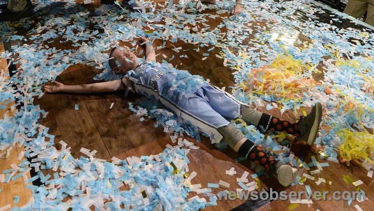 """Aiden Williams, the grandson of UNC head coach Roy Williams makes a """"confetti angel"""" on the floor as the Tar Heels celebrate their national champioship. UNC beat Gonzaga 71-65 Monday, April 3, 2017 at the NCAA Final Four National Championship game in Glendale, Az. at the University of Phoenix Stadium."""