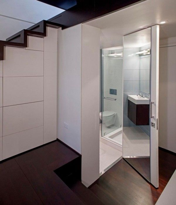 Storage initiatives have been thoughtfully incorporated into the space- limited though it is- and in much the same way as the segmented white wall beneath the rich wooden staircase conceals an ample amount of storage, it sits atop a simple but functional bathroom that, with mirrored walls, appears larger.