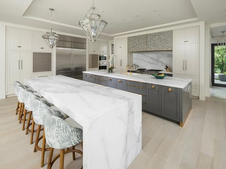 A large contemporary kitchen features a Calcutta marble waterfall kitchen island seating five white and gray upholstered counter stools sat on blonde wood floors lit by two nickel and glass diamond pendants hung from a tray ceiling.
