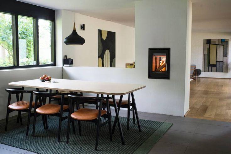 Parret fjernede den oprindelige pejs og ændrede muren til stuen til en halvmur for at skabe lys og luft mellem spisestue og køkken på den ene side og stuen på den anden. Spisestuestolene er en sjælden Wegnermodel, og lampen er en original Jo Hammerborg. Foto: Ida Munch