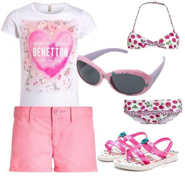 Simpatico outfit sulle tonalità del rosa composto da costumino due pezzi con lamponi e ciliege, t-shirt Benetton con stampa, pantaloncini corti rosa, occhiali da sole fioriti e sandalini in gomma marca Havaianas.