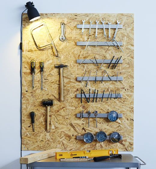 On a wooden board above a work table, several magnetic knife racks hold screw, nails, drill bits and other metal work tools.