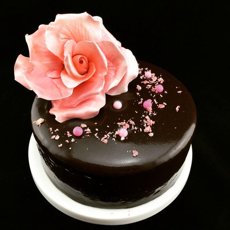 Elegant chocolate mirror glaze cake with pink sugar rose. 100% vegan.