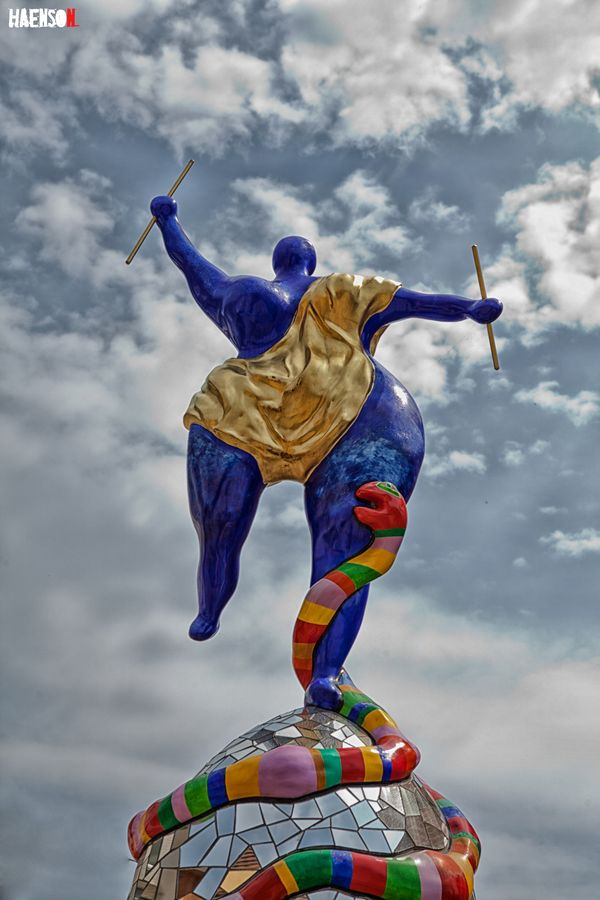"""Niki de Saint Phalle (1830-2002) was a French sculptor, painter, and film maker. In 1966, Saint Phalle collaborated with fellow artist Jean Tinguely and Per Olof Ultvedt on a large-scale sculpture installation, """"hon-en katedral"""" (""""she-a cathedral"""") for Moderna Museet, Stockholm, Sweden. The outer form of """"hon"""" is a giant, reclining 'Nana', whose internal environment is entered from between her legs. The piece elicited immense public reaction in magazines and newspapers throughout the world."""