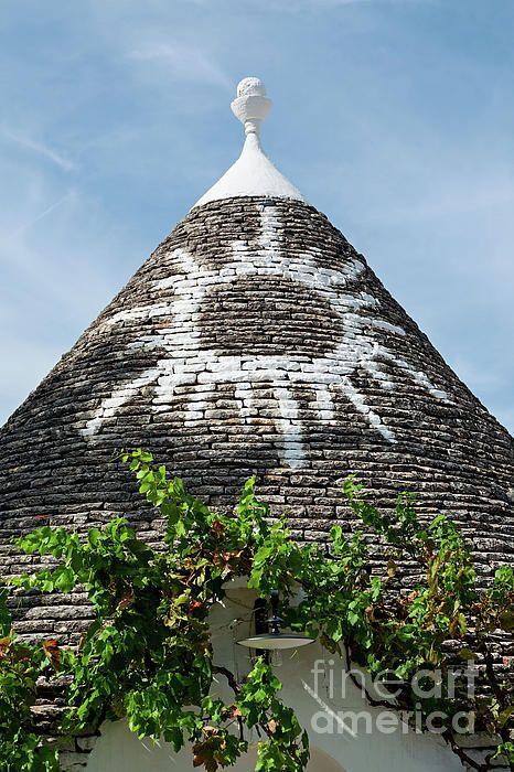 Symbol in the Trullo conical rooftop in Alberobello under a blue sky, Puglia, Italy