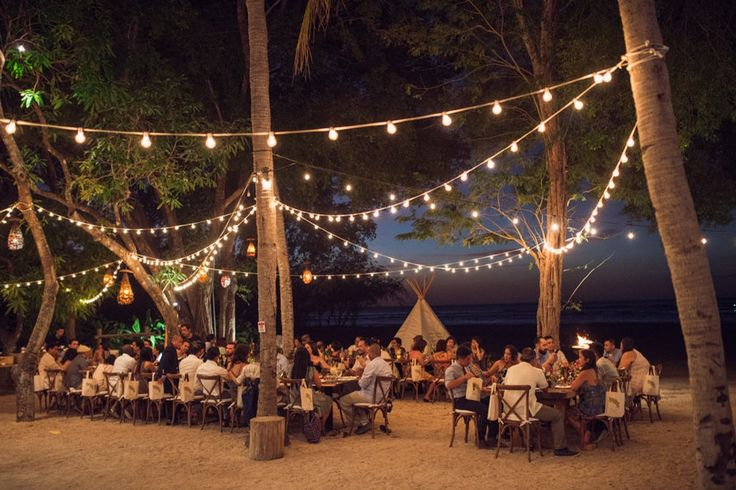 Beach wedding reception with x back bistro chairs and tee pee on the background. Tamarindo, Costa Rica.