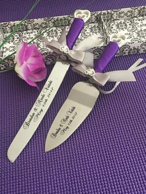 """Personalized Laser engraved interlocking hearts design cake knife-server set is perfect for wedding, anniversary, birthday. house warming, and any special occasion. The Handle is wrap with Purple haze satin with Silver bow and a heart shape rhinestone on top of the bow. Dimensions: 12 1/4"""" x 1"""" cake knife, 10.5"""" x 2"""" server. You can have your own quote engraved on the knife with extra cost (no more than 12 words). Please contact me for detail. The material's color may be slightly diffe..."""