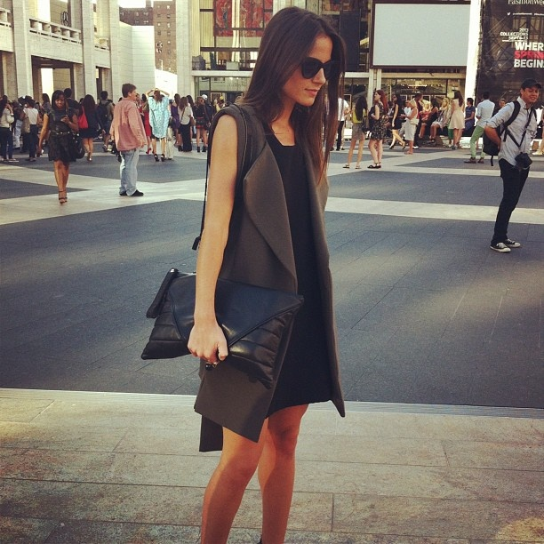 Khaki vest over a black ensemble topped off with an oversized clutch. Perfect #NYFW outfit!