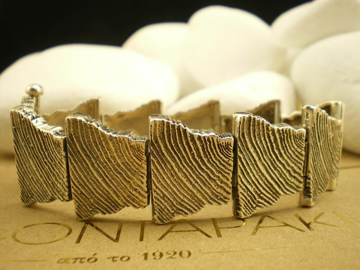 """Fascinating bracelet from the A. Leondarakis jeweler's that is part of the """"Wood"""" collection.         Its design was inspired by the crevices found in tree trunks and was subsequently named """"Wood"""". It features eleven embossed elements with an oxidized like surface (by reticulation) bound together by sturdy handcrafted hinges that allow the bracelet to securely and gracefully engulf the wrist."""