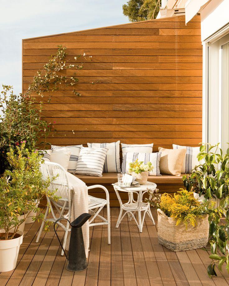 Pequeña terraza con estar, pared con lamas de madera, suelo entarimado, banco, cojines a rayas y sillas de fibras vegetales