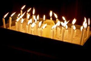 Trauerrituale: Vigilkerzen, die in ca. 30-45 Minuten herunterbrennen werden zu Beginn der Trauerfeier von den Besuchern entzündet und in die Sandschale gesteckt