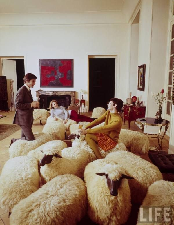 Group of Parisians in a room with sheep-shaped chairs designed by Francois-Xavier Lalanne --1967.