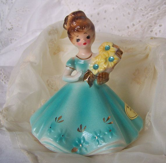 Sweet vintage Josef Original March Birthday Girl. Young girl in a beautiful aqua dress trimmed in gold holds a bouquet of yellow flowers with 3 aquamarine gemstones center of daisy. Girl has brown eyes and brown hair. March Aquamarine by Josef sticker still attached as well as paper label reading: March  Aquaarine means courage Im brave as I can be and never say that Im afraid of anything I see.  Bottom of figurine has the Josef Originals logo.  March birthday girl figurine stands 4 inches…
