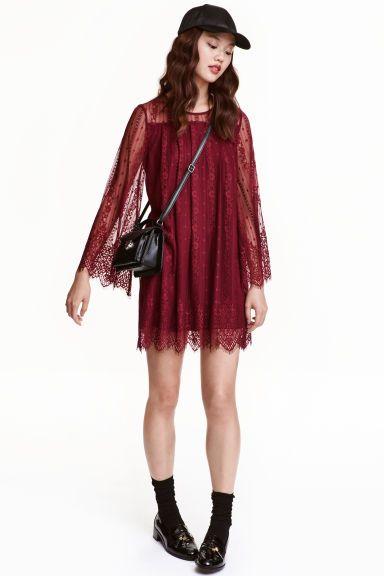 Korte kanten jurk: Een korte kanten jurk met een schouderpas met platte plooien eronder. De jurk heeft lange trompetmouwen, een splitje met een knoop in de nek en een onafgewerkte schulprand aan de onderkant en onder aan de mouwen. Het voor- en achterpand zijn gevoerd.