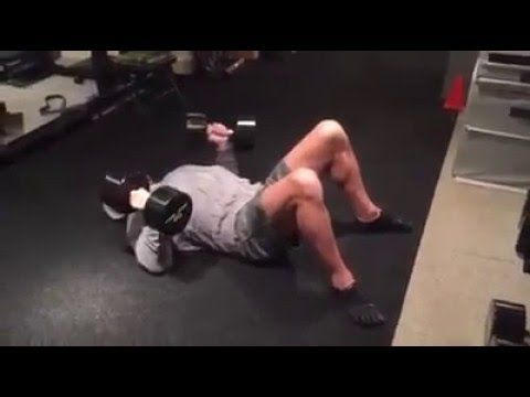 Triple H Exercising in gym with dumbbells