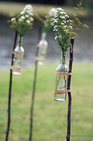 Super easy DIY :) Clear pop or beer bottles with a few sprigs of flowers on a wooden stake...