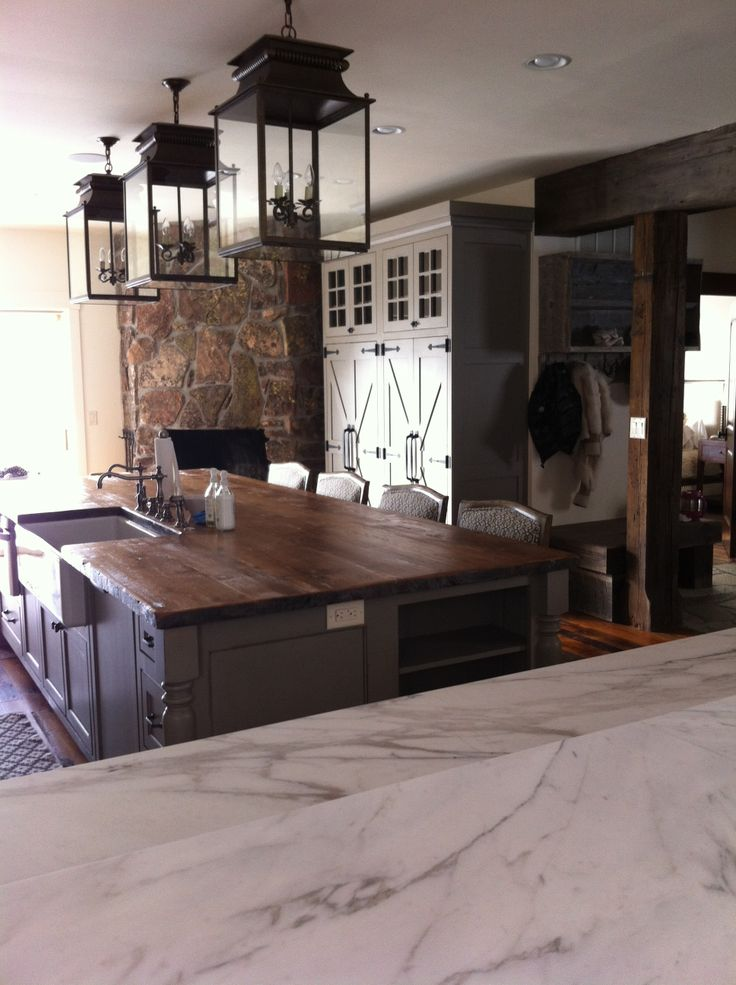 The Kitchen - Custom Pantry made to look like something you would find in an old farmhouse kitchen by Specialty Woodworks Company of Hamilton, Montana Lighting from Circa Lighting, Island Top made from reclaimed lumber other counter tops made from honed calacatta marble.
